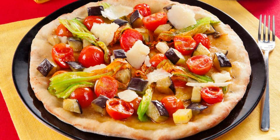 Mediterrane Pizza mit Kirschtomaten, Aubergine, Zucchiniblueten und Parmesan