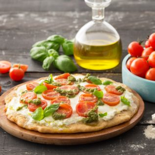 Pizza mit Tomaten und Basilikum Pesto